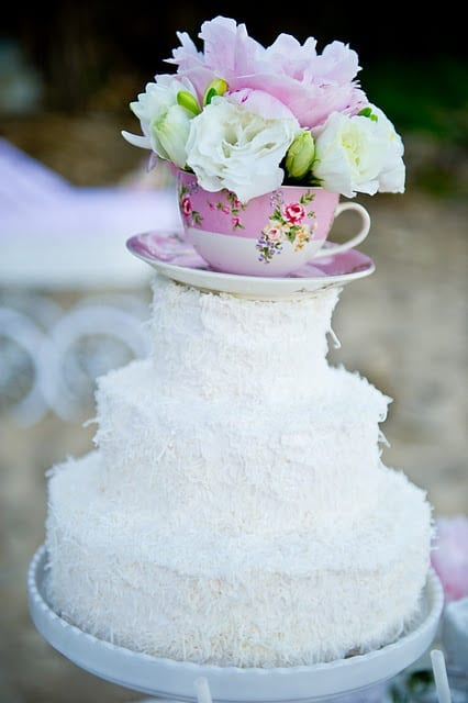 Love this tea party cake! Coconut covers any frosting imperfections. Use a real tea cup as a topper...what a lovely idea!